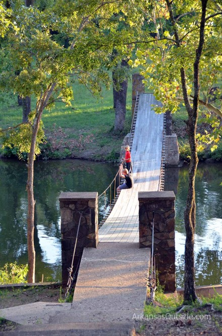 A couple of kids fishing from the swinging bridge.