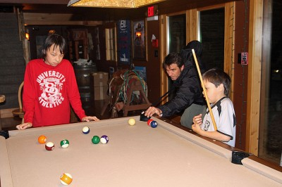Dr. Wayne schooling the boys in the finer points of pool.