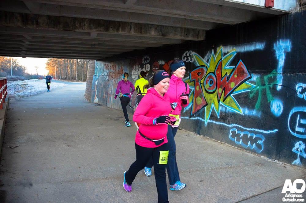 Runners pass each other under the overpass.