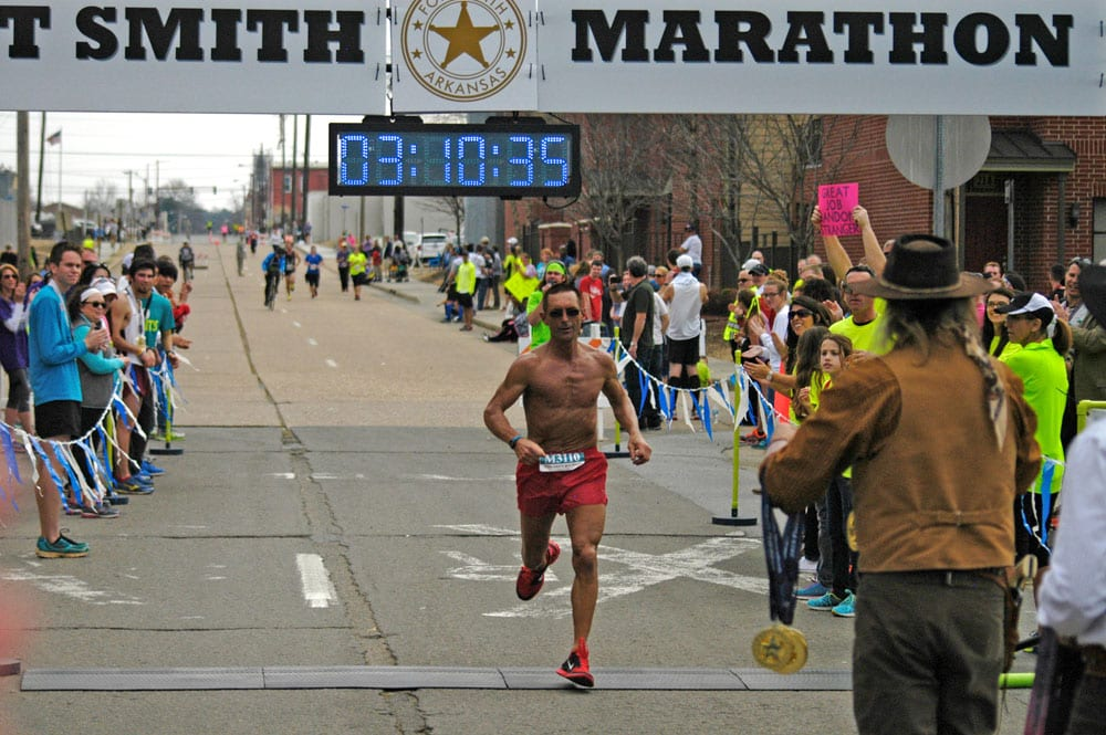 Randy Johnson of Fayetteville crosses the finish line to win the inaugural Fort Smith Marathon.